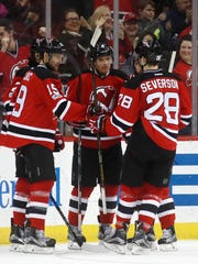 Devils players celebrate a goal by Taylor Hall, center, during the first period of a game against the Winnipeg Jets, Tuesday, March 28, 2017, in Newark.