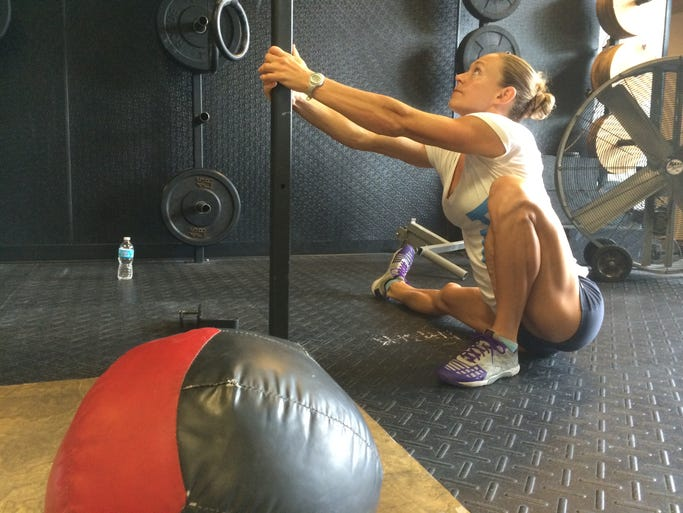 Talayna Fortunato stretches before a workout at CrossFit Real Fitness in Naples. Fortunato is one of three local athletes competing at the CrossFit Games in Carson, Calif. this weekend.