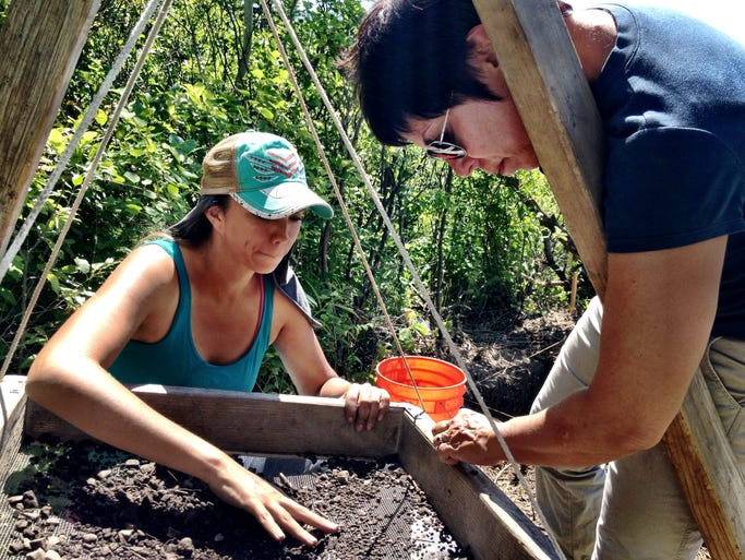 Maria Zedeno, a University of Arizona archaeologist, reviews findings with Geri Osborne of the Blackfeet Nation. Osborne is sifting through dirt looking for signs of ancient human occupation of the site in Glacier National Park near St. Mary.