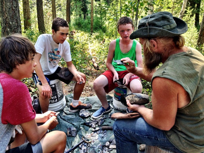 """Carver Gilman, Reed Miller and John McDonnell learn flint knapping from Luc Tunkel. They made arrowheads, axes and knife blades. The campers learn basic skills with broken glass before they take on obsidian. """"There's something very satisfying about using a busted TV to make stone age tools,"""" Tunkel said."""