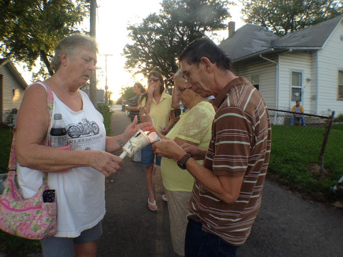 Neighbors gathered for a candlelight vigil Friday, August 22, 2014 outside the house in the 1500 block of N. 16th Street in Lafayette where 54-year-old Rick Couch was found beaten to death Wednesday.