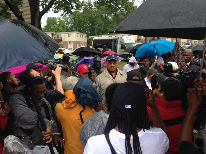 Jesse Jackson stood in the rain with protesters in Ferguson Saturday.