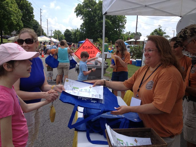 Jennifer Witkowski and her daughter Virginia, 13, pick up a map and tote bag from Rhonda Burnette at the entrance to Coopertown's Barrel Festival on Saturday, June 7, 2014.