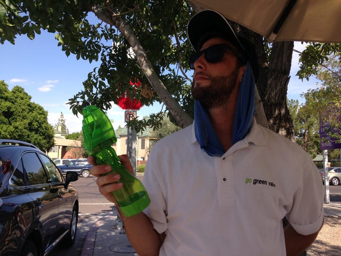 Local valet, 22-year-old Chase McIntyre, cools off with a towel and fan that squirts water.