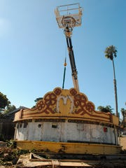 In this photo from August 2013, a crane lifts the then-73-year-old Mayfair Theater marquee out of the dirt at Figueroa Street and Thompson Boulevard in Ventura, where it had sat for a decade. It was the first step in getting the marquee to the U.S. Seabee Museum at Naval Base Ventura County Port Hueneme. The renovation has been completed and the marquee is now installed.