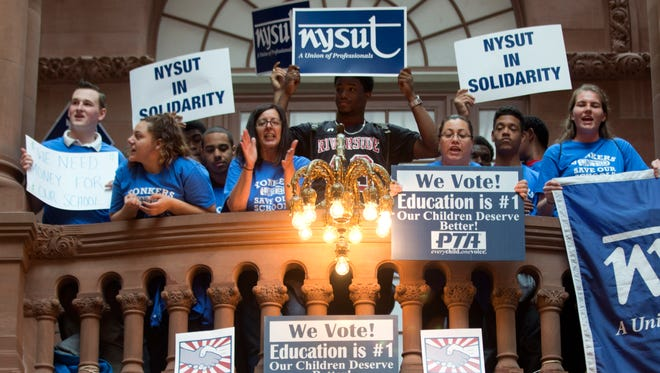 Supporters of the Yonkers school district hold signs during a rally on the Great Western Staircase at the Capitol on Tuesday in Albany, N.Y.