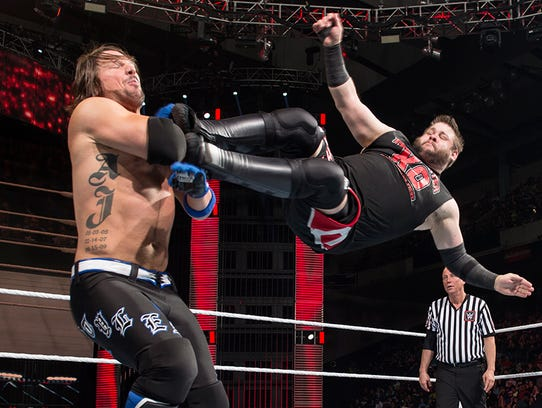 Kevin Owens drop-kicking  AJ Styles.