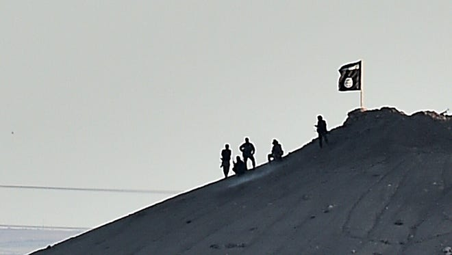 Alleged Islamic State (IS) militants stand next to an IS flag atop a hill in the Syrian town of Ain al-Arab, known as Kobane by the Kurds, On Sept. 6, 2014.