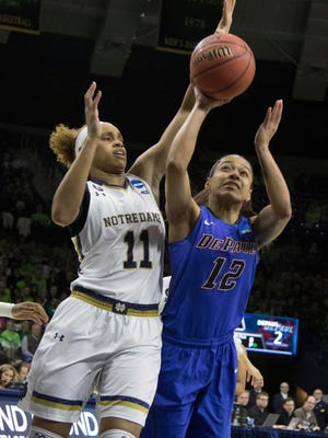 Mar 22, 2015; Notre Dame, IN, USA; DePaul Blue Demons guard Brittany Hrynko (12) shoots while Notre Dame Fighting Irish forward Brianna Turner (11) defends  in the first half of the second round game of the 2015 Women's NCAA Tournament at Edmund P. Joyce Center. Mandatory Credit: Trevor Ruszkowski-USA TODAY Sports