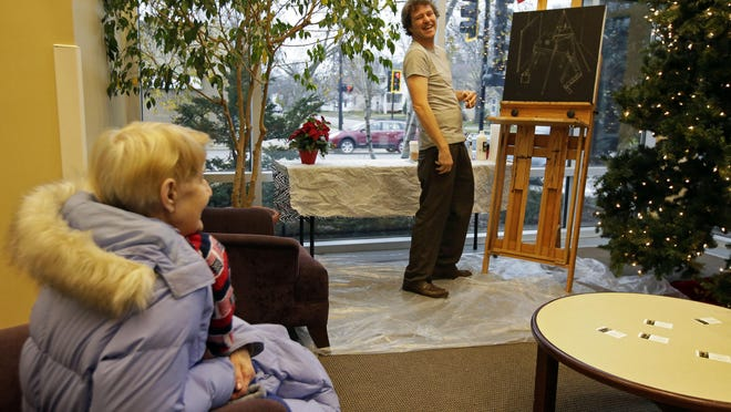 Artist Leif Larson talks with Jane Phillips of Menasha while working on a painting Dec. 3 at the Elisha D. Smith Public Library in Menasha.