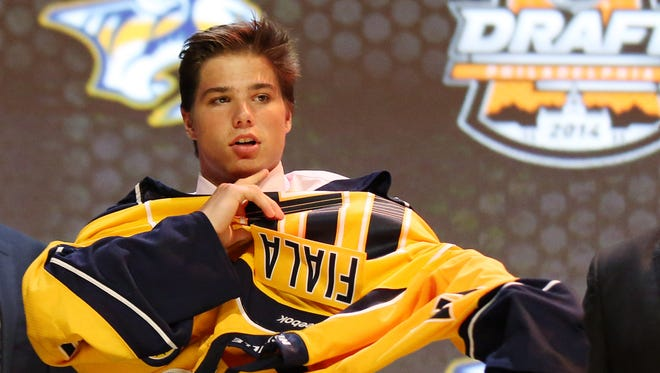 Kevin Fiala puts on a Predators sweater after being drafted 11th overall on Friday.