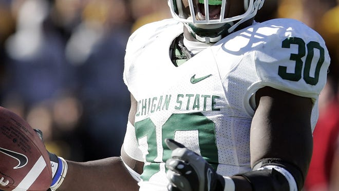 Michigan State's Jehuu Caulcrick celebrates after a 3-yard touchdown run during the first overtime of a football game against Iowa on Saturday, Oct. 27, 2007, in Iowa City, Iowa. Iowa won 34-27 in two overtimes.