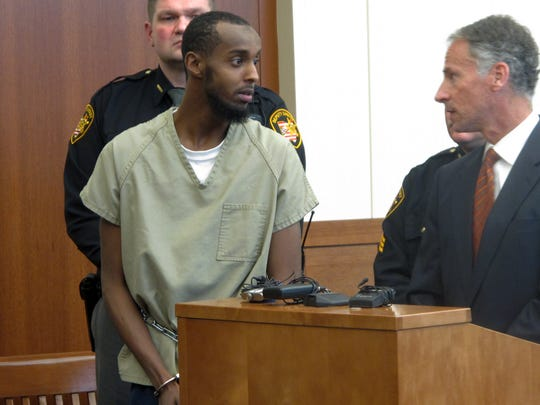 Abdirahman Sheik Mohamud, left, speaks with his defense
