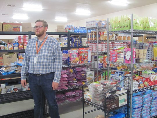 Switchpoint Food Pantry Manager Weston Zimmerman talks about the new facilities for storing items that will be delivered to impoverished members of the community following a ribbon-cutting ceremony Wednesday.