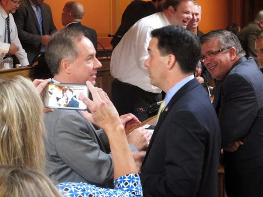 Gov. Scott Walker talks with Republican Assembly Speaker Robin Vos, left, after telling lawmakers he supports changes to the law governing hiring and firing of state workers on Sept. 24, 2015 at the State Capitol in Madison.