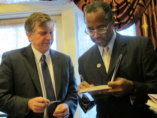 Ben Carson signs a book for Maryland state Del. William Frank in Annapolis on March 8, 2013.