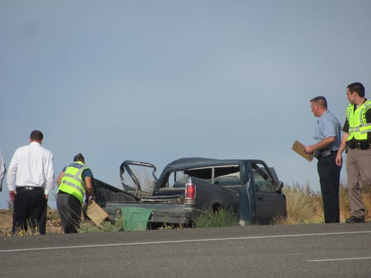 Investigators look at the wreckage of a blue pickup