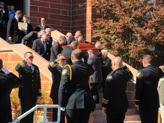 Law enforcement members comprising an honor guard salute as casket bearers carry former St. George Mayor Karl Brooks' coffin from the St. George Tabernacle on Saturday, which would have been Brooks' 80th birthday.