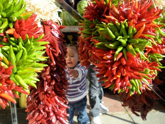 A young chile fan is attracted by colorful wreaths