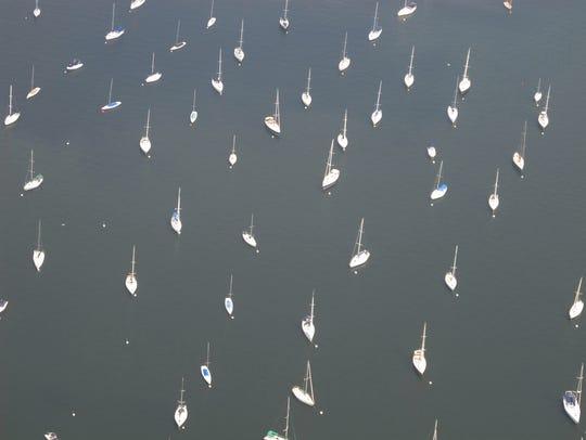 Sailboats anchor in a Lake Champlain bay in July.