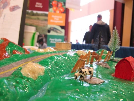 A model cow makes it way towards an un-fenced portion of a stream Wednesday in a watershed model at the Vermont Farm Show in Essex Junction.