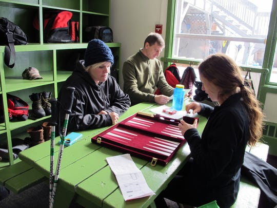 Nicole Luther, left, a veteran who suffers from post-traumatic stress disorder, and program coordinator Kelly Walsh, right, play backgammon as they take a break from skiing A group of service members of the Gulf, Iraq and Vietnam wars say the weekly gatherings through the Vermont Adaptive Ski & Sport programs help get them out of the house, connect with other people and take their mind off of their post-traumatic symptoms. At center rear is David Jamison, a veteran that participates in the program and also suffers from PTSD.
