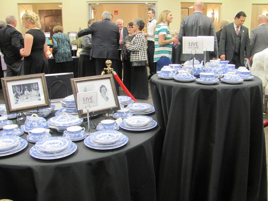 A china set prepared for auction serves as a centerpiece as guests mingle Friday during the annual Fire and Ice gala at the SunRiver community center.