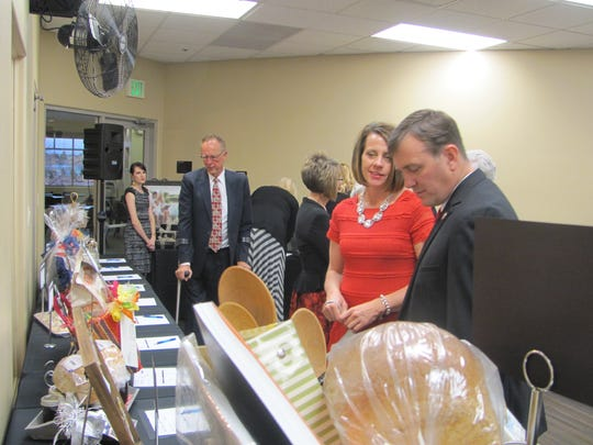 Dixie State University President Biff Williams, right, and his wife Kristin look over silent auction items Friday during the annual Fire and Ice gala at the SunRiver community center.