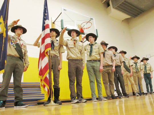 Boy Scouts from Troop 904 salute at the end of the