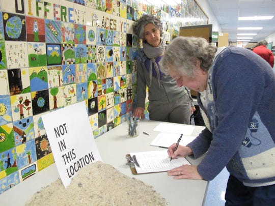 Early March: Jeanne LaClair, a Shelburne resident, signs a petition against a proposed rail-transfer depot in advance of Monday's pre-Town Meeting Day gathering. Opponents of the project, including Roberta Nubile, at left, set up a display table at Shelburne Community School, including a small mound of road-salt – which would constitute some of the freight to be stored next to the LaPlatte River.