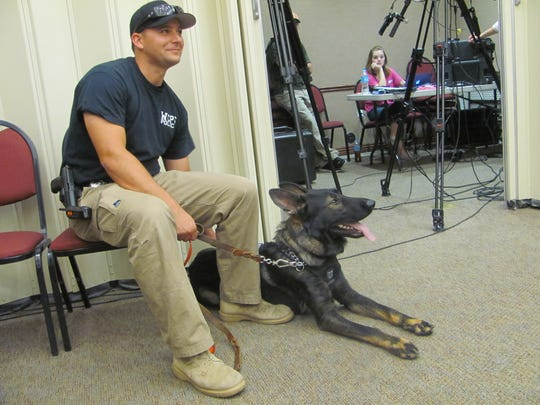 Washington City Officer Ryan Ericksen and his K-9 partner Tank visit with audience members at the Washington City Council meeting, where Police Chief Jim Keith presented a plaque to thank Tank's trainers.