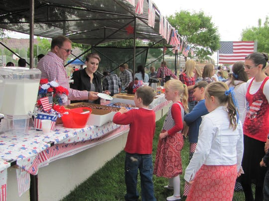 Centennial Park residents line up for food during the community's Fourth of July celebrations Saturday, south of Colorado City. Centennial Park polygamists separated from the Fundamentalist Church of Jesus Christ of Latter Day Saints 30 years ago.