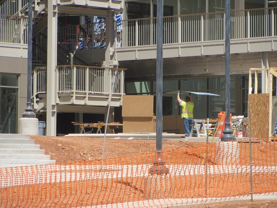 A construction worker carries materials at Dixie State