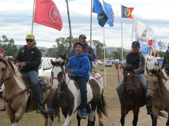 Horseback riders make their way through an encampment