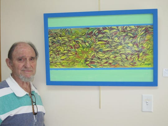 Carl Rantz stands with one of his works in an exhibit