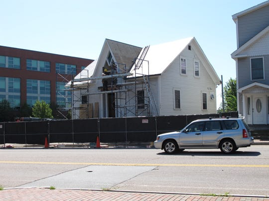 """Recent history: An historic house in Winooski is prepared for transport to Burlington on July 27, 2016. The site is under construction for a new multistory """"City Lights"""" residential and commercial development. The brick Vermont Community College building is seen at the far corner of East Allen Street and Abenaki Way."""