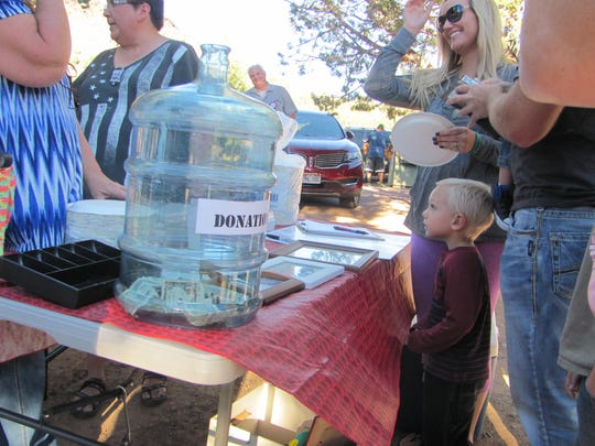 Well-wishers gather around a donation bucket during a fundraiser for Bunkerville's Bundy family members at the Veyo Park on Saturday.