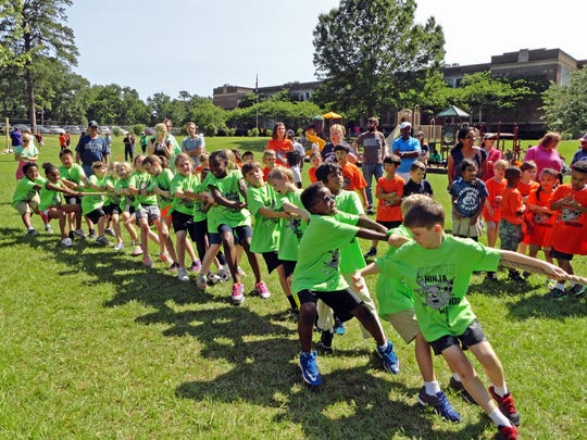 Parents, teachers and student watch the activity during Fairfield's Field Day Tug of War.