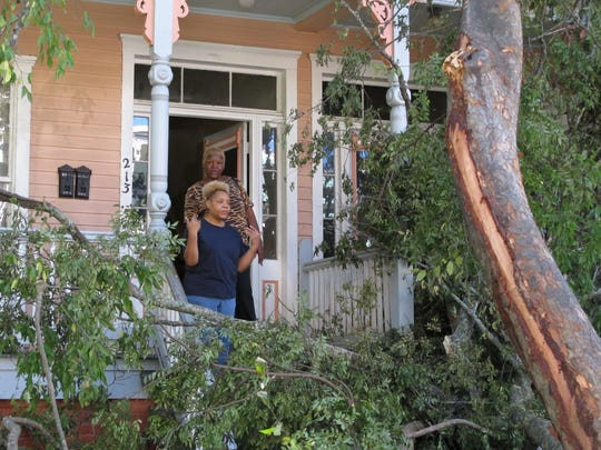 Sharon Kelsey, front, and her cousin, Pamela Williams, stand on the front port of the Victorian home in Savannah, Ga., where Kelsey lives in a first floor apartment Monday, Oct. 10, 2016. A large tree crashed across the front of the house as Hurricane Matthew raked the Georgia coast over the weekend. Matthew did extensive damage to the signature tree canopy in Savannah.