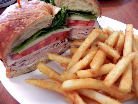 Add cranberry sauce to a turkey club sandwich.
