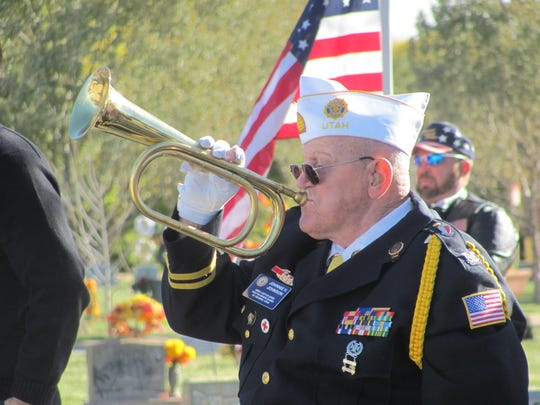 American Legion Post 90 Sgt.-at-arms Johnnie Johnson plays Taps during a Pearl Harbor Day ceremony Wednesday at Tonaquint Cemetery.