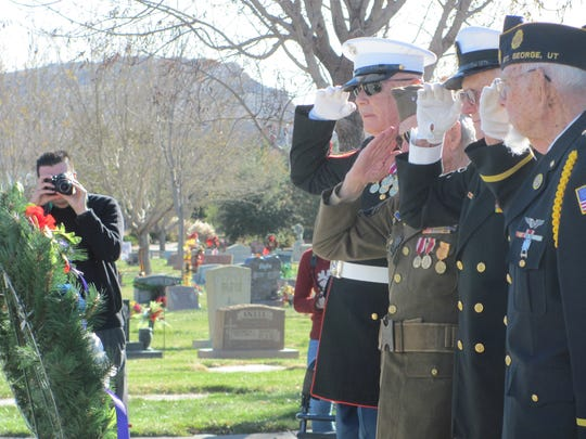 Marine Sgt. Maj. Bill Head, Army veteran Ridge Bemis, Navy Master Chief Petty Officer Robert Thurman and Air Force veteran Doug Johansen salute after placing a wreath at the Pearl Harbor survivors monument in Tonaquint Cemetery on Dec. 7, 2016.
