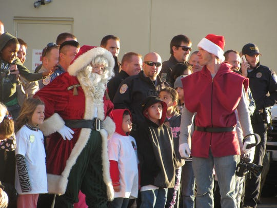 Children and law enforcement officers join Santa Claus for a photo op Saturday during the annual Shop With a Cop event in Hurricane.