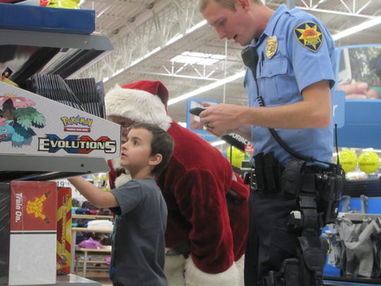 Santa Claus and St. George Police Officer Zack Bahlmann help Adonis Doss search for a Pokemon gift Saturday during the annual Shop With a Cop event in St. George.