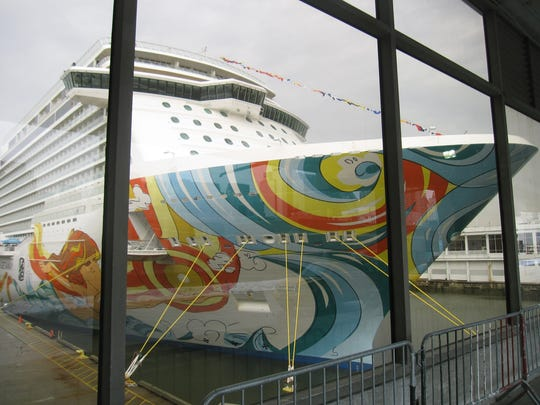 Norwegian Cruise Line's colorful new cruise ship Norwegian Getaway seen behind a glass wall at Manhattan's Pier 88 on the Hudson River on Monday, Jan. 27, 2014. The ship stopped in New York City Monday and will return later this week as a floating hotel for Super Bowl fans before heading to its new homeport in Miami. The ship has a tropical theme reflected in restaurants and decor. (AP Photo/Beth J. Harpaz)