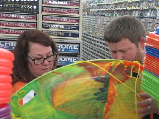 Leann Rumsey and son Josh Rumsey study various styles of sleds at White Jones Hardware store Friday.