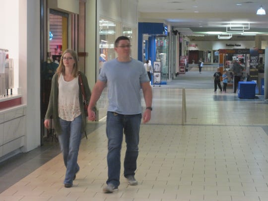 A couple walks through the quiet Anderson Mall on Friday night.