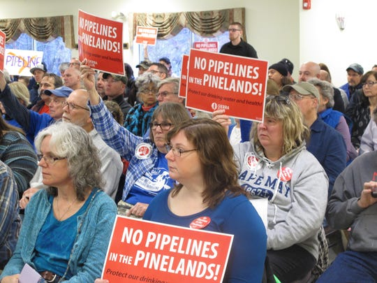 Opponents of a natural gas pipeline proposed to run through the federally protected New Jersey Pinelands region hold signs against it during a public hearing on the proposal in Pemberton N.J. on Tuesday Jan. 24, 2017.