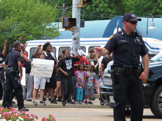 A police officer controls traffic as Black Lives Matter protesters wait to cross the street in front of Graceland, the former home of Elvis Presley, on Tuesday, July 12, 2016, in Memphis, Tenn. (AP Photo/Adrian Sainz).