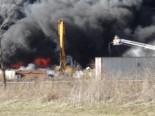 Flames are visible as fire crews battle the Thursday morning blaze at Sims Brothers Recycling.